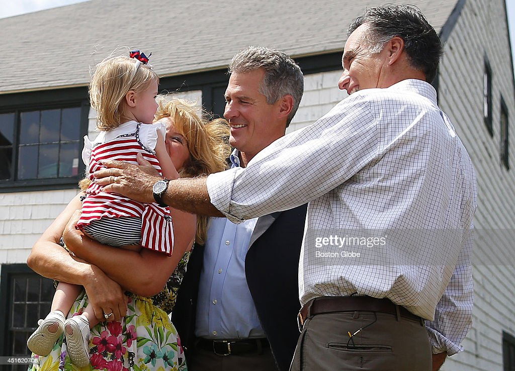 Left to right, Gail Huff holds her 20-month-old niece Anna Lee Stohl as Scott Brown and Mitt Romney lean in to greet her during a campaign event at Bittersweet Farm in Stratham, New Hampshire July 2, 2014.