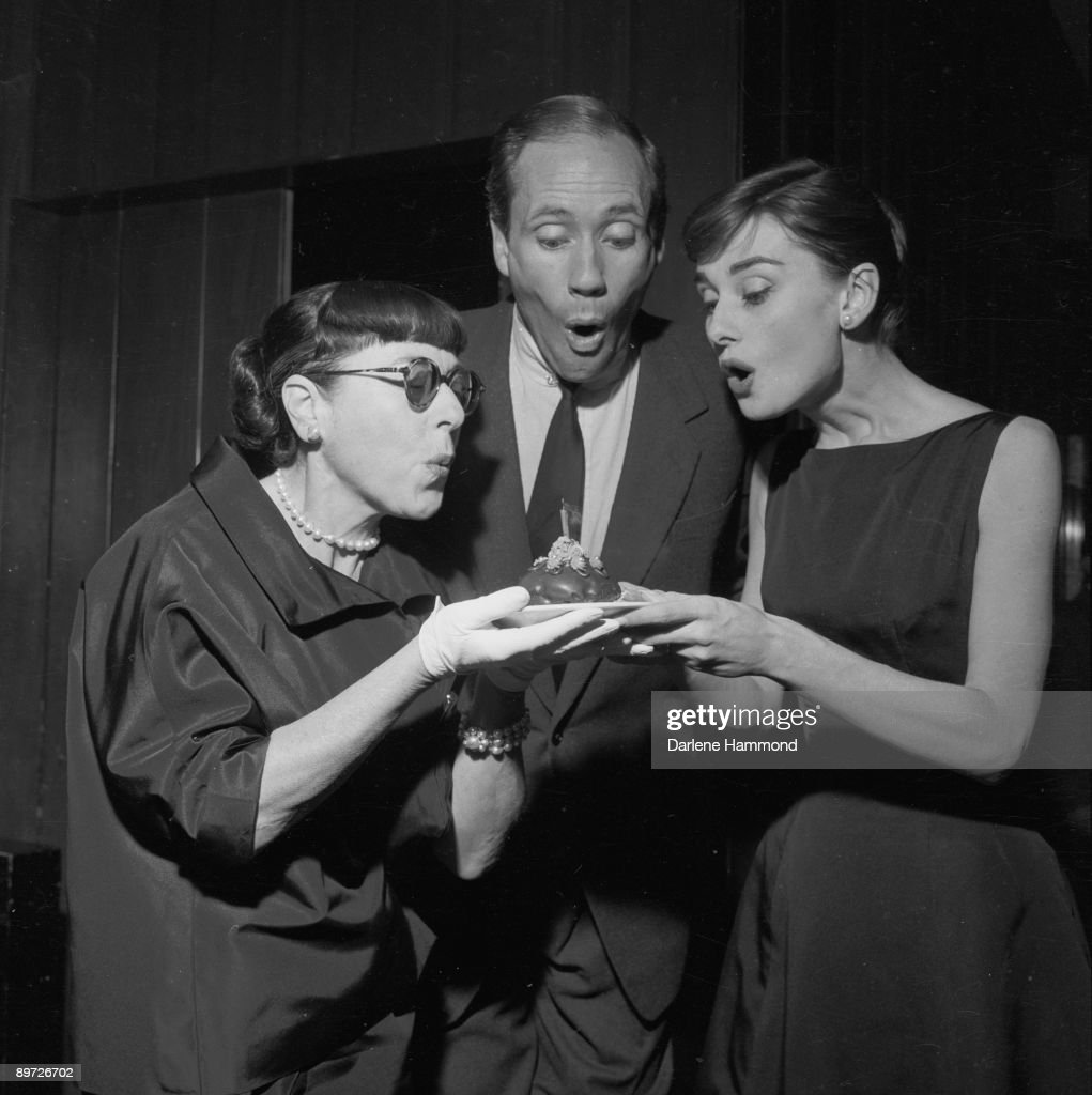 Hollywood costume designer Edith Head American actor Mel Ferrer and his wife Actress Audrey Hepburn blowing out the candle on Head's birthday cake at...