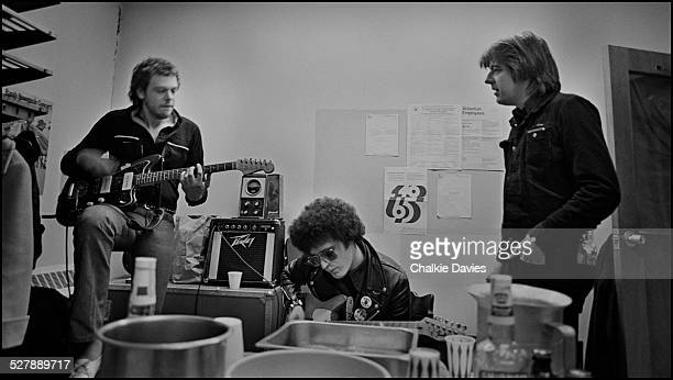 Martin Belmont of British rock group The Rumour New Musical Express journalist Charles Shaar Murray and English singersongwriter Nick Lowe backstage...