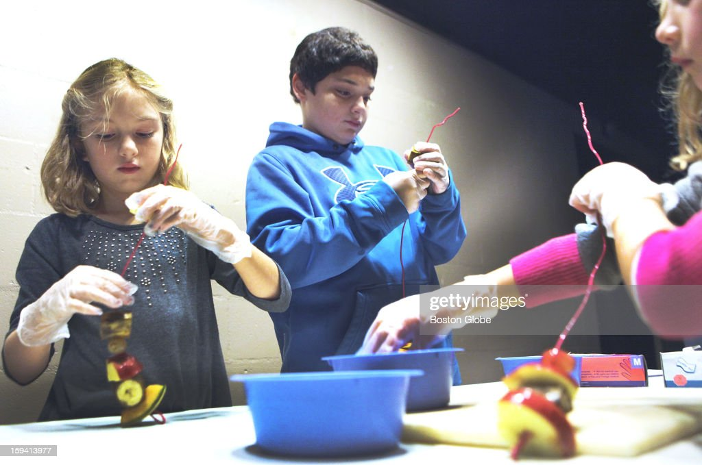 Left to right, Miriam Parrucci, 8, brother, John, 13, of Havertown, Pa., and Juliet Coleman, 6, of Amherst, made fruit kebabs for Ruwenzori long-haired fruit bats on exhibit at Franklin Park Zoo in Boston, Saturday, Dec. 8, 2012.