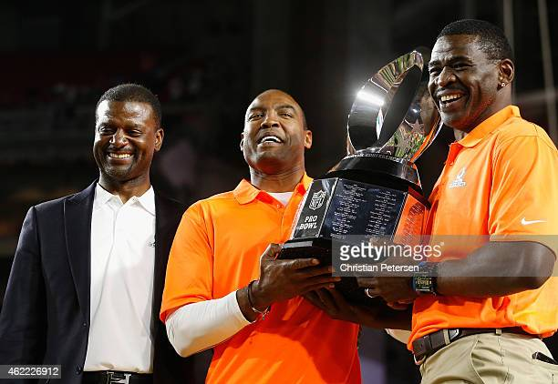 Left to right NFL vice president Merton Hanks Darren Woodson and Michael Irvin pose with the Pro Bowl trophy after the 2015 Pro Bowl at University of...