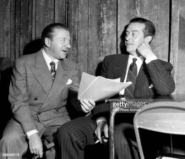 Left to right producer Charles Vanda and actor Ray Milland go over script of The Uninvited on CBS Radios Theater of Romance Originally broadcast on...