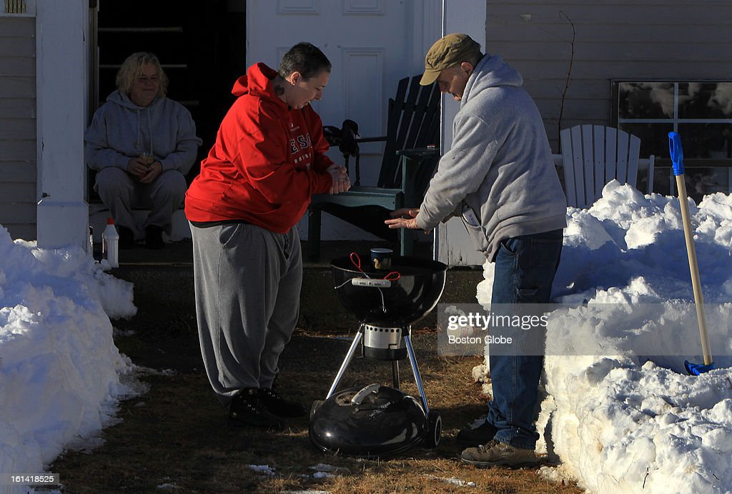 Left to right, Robin Donehoo, Stacey Demary, and David Walmsley, heat up a grill outside their Ocean Street apartments as they get ready to prepare a meal for their families on Sunday, Feb. 10, 2013, after a blizzard hit New England.