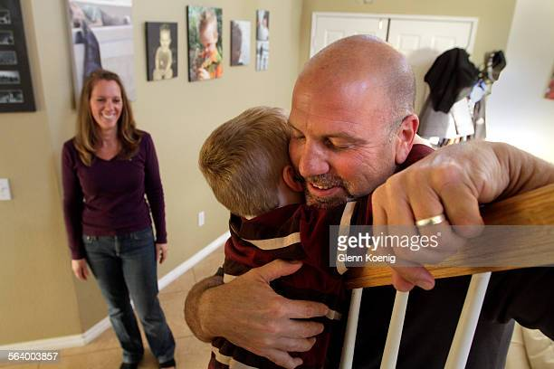 CA MARCH 21 2013 Left to right Russell Poland gets a hug from his son Wyatt age 5 as Michele looks on at their home in Temecula on March 21 2013...