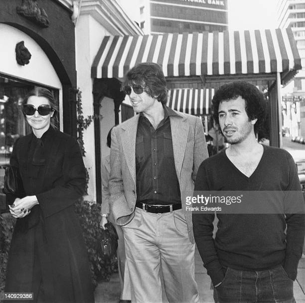 singer Michelle Phillips actor Warren Beatty and record executive David Geffen leaving the Cock n' Bull restaurant on Sunset Boulevard Hollywood...