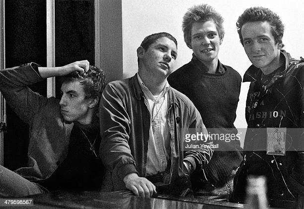 singer Vic Godard of Subway Sect their roadie Barry Auguste with bassist Paul Simonon and singer Joe Strummer of 'The Clash' backstage at a concert...