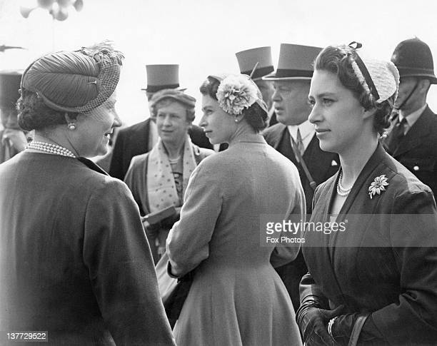 the Queen Mother Queen Elizabeth II and Princess Margaret at the Derby Epsom Downs Racecourse Surrey 25th May 1955 At centre right is politician and...