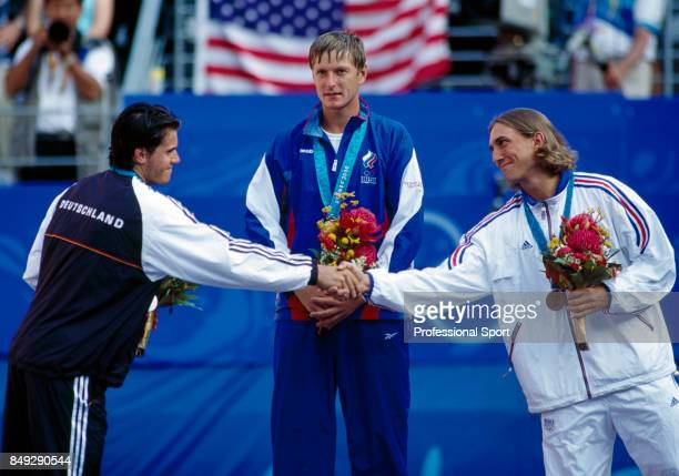 Tommy Haas of Germany Yevgeny Kafelnikov of Russia and Arnaud Di Pasquale of France during the medal presentation ceremony for the men's singles...