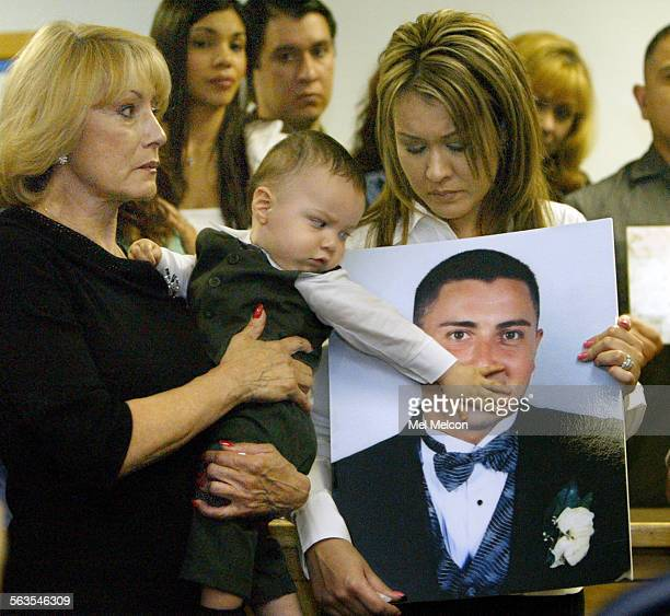 left to right–Sergio Reyes' mother Esther Munguia his son Brandon Reyes 11 months and wife Celina Reyes holding wedding photo of Sergio during press...