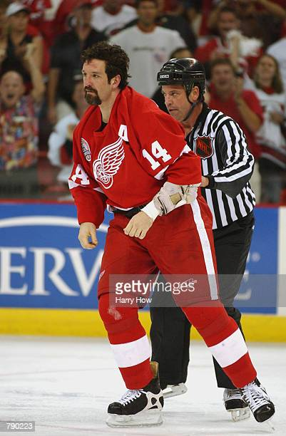 Left Wing Brendan Shanahan of the Detroit Red Wings is escourted to the penalty box by linesman Dan Schachte after a tussle with center Josef Vasicek...
