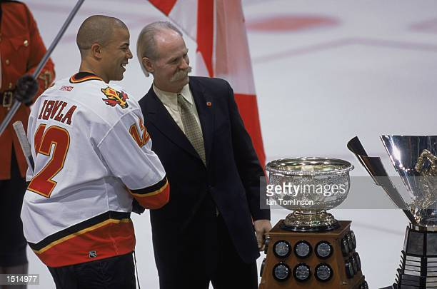Left wing Jarome Iginla of the Calgary Flames poses with former Flames great Kent Nilsson in front of the Art Ross Trophy and the Maurice 'Rocket'...