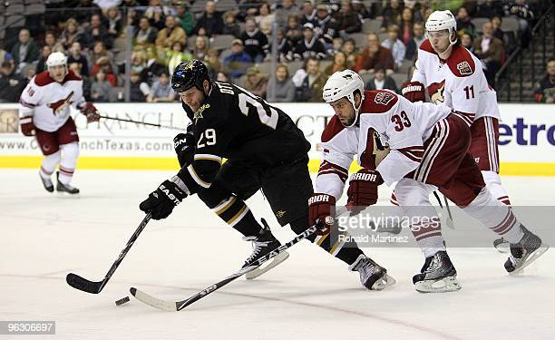 Left wing Steve Ott of the Dallas Stars skates the puck against Adrian Aucoin of the Phoenix Coyotes in the third period at American Airlines Center...