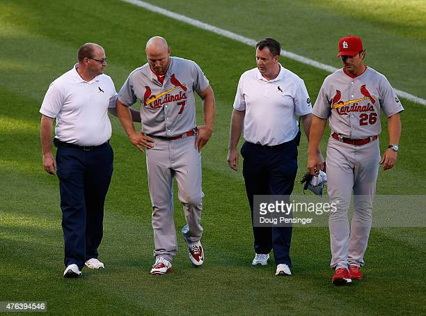 Leftfielder Matt Holliday of the St Louis Cardinals is escorted off the field by manager Mike Matheny of the St Louis Cardinals and the trainers...