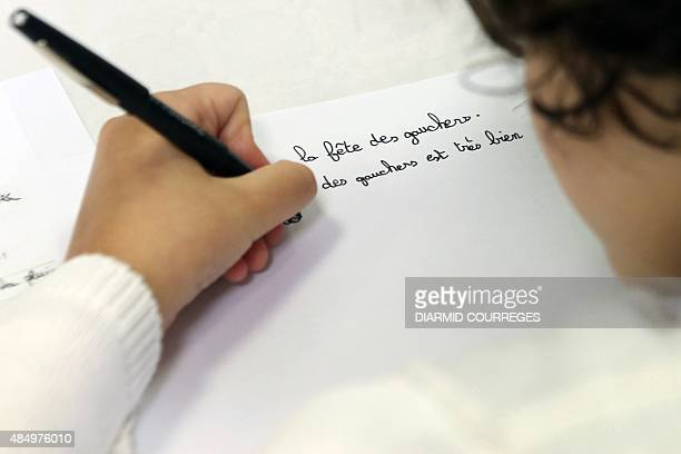 A lefthanded child writes in the Salle du Pont du Buy in Brivela Gaillarde where writing and cooking workshops were organised and objets for the...