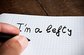 closeup of a young left-handed man handwriting the text I am a lefty in a notepad placed on a wooden table