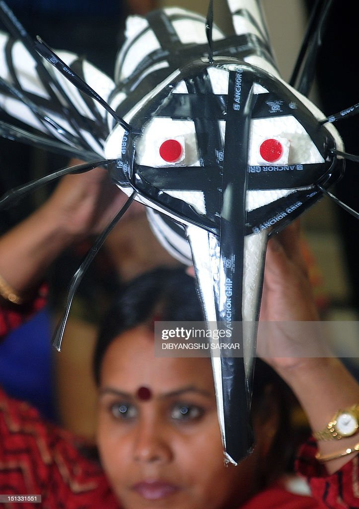 Leftist councilors of Kolkata Municipal Corporation (KMC) hold a model of a 'dengue' mosquito as they sit under a mosquito net during a protest at the KMC building in Kolkata on September 6, 2012. Dengue is swarming in the city this season and doctors agree that it may be the worst outbreak since 2005 with hospitals on the fringes admitting scores of dengue patients in the last few days. AFP PHOTO/Dibyangshu SARKAR