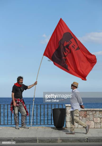 A leftist demonstrator holding a flag of Chinese communist revolutionary Mao TseTung pauses during a march in which several thousand partook to...