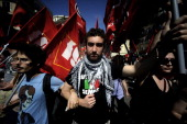 Leftist demonstrators hold flags as they march in downtown Rome to protest against Italian Prime Minister Mario Monti's government and its reforms on...