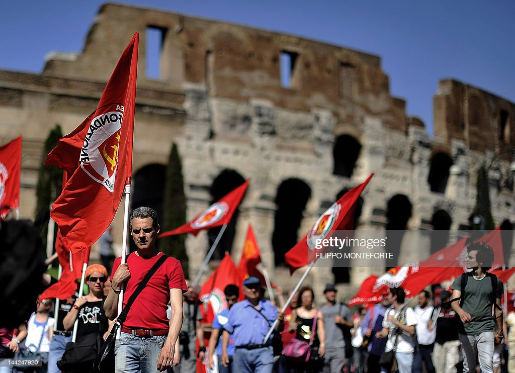 Leftist demonstrators hold flags as they march in front of the ancient Colosseum in downtown Rome to protest against Italian Prime Minister Mario...