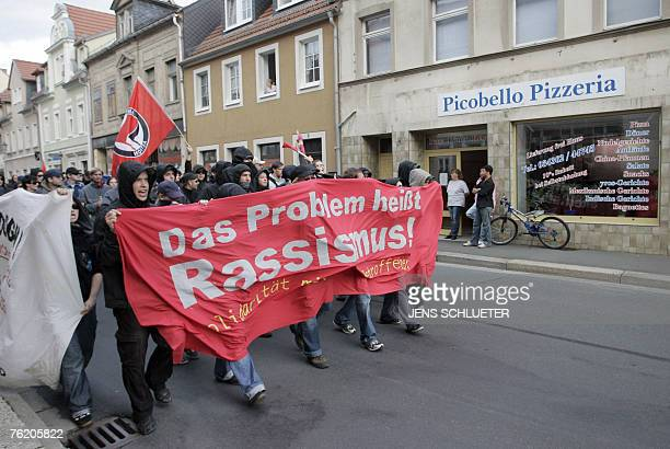 Leftist demonstrators walk past the pizzeria in Muegeln 21 August 2007 where 8 Indian nationals had taken refuge after being pursued and beaten by a...