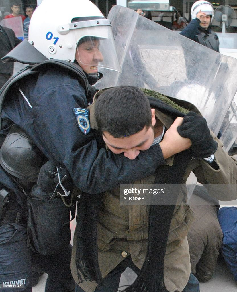 A leftist group member bites the arm of a Turkish riot policeman during a protest against the deployment of NATO Patriot missiles, on January 21, 2013, in front of a US military base at Incirlik in Adana. Two Patriot missile batteries each arrived from Germany and the Netherlands on January 21 in Turkey as part of a NATO mission to protect Turkish borders from any spillover of the conflict in neighboring Syria.