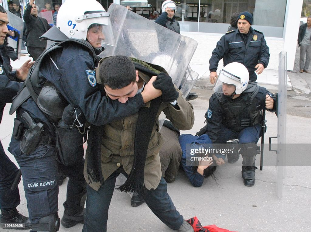 A leftist group member bites the arm of aTurkish riot policeman during a protest against the deployment of NATO Patriot missiles, on January 21, 2013, in front of a US military base at Incirlik in Adana. Two Patriot missile batteries each arrived from Germany and the Netherlands on January 21 in Turkey as part of a NATO mission to protect Turkish borders from any spillover of the conflict in neighboring Syria.