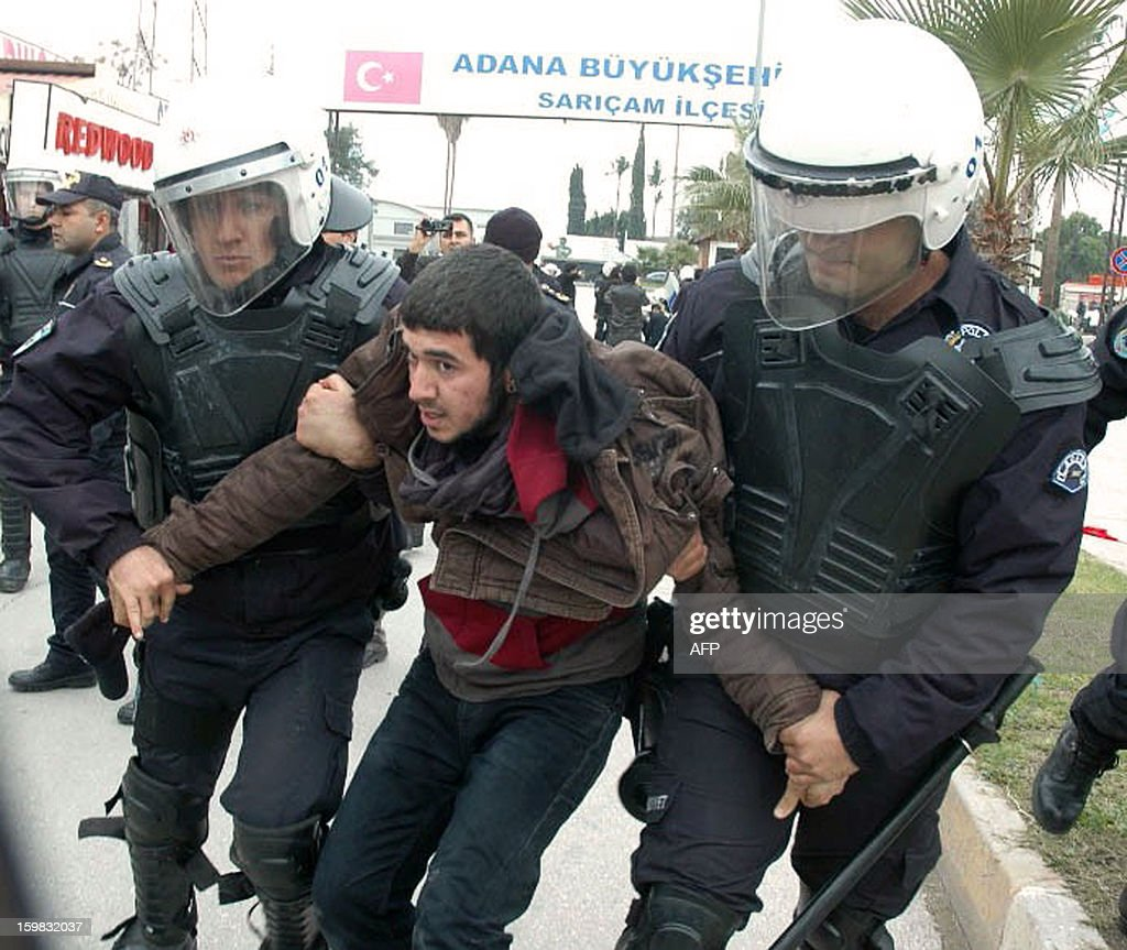 A leftist group member is arrested by Turkish riot policemen during a protest against the deployment of NATO Patriot missiles, on January 21, 2013, in front of a US military base at Incirlik in Adana. Two Patriot missile batteries each arrived from Germany and the Netherlands on January 21 in Turkey as part of a NATO mission to protect Turkish borders from any spillover of the conflict in neighboring Syria. AFP PHOTO / IHLAS NEWS AGENCY