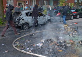 Leftist protesters walk past a burned out car during a march by neoNazis on June 2 2012 in Hamburg Germany Thousands of protesters took to the...