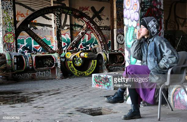 A leftwing activist speaks on her mobile phone inside the ruins of a former ice factory known locally as the Eisfabrik as threat of eviction for the...