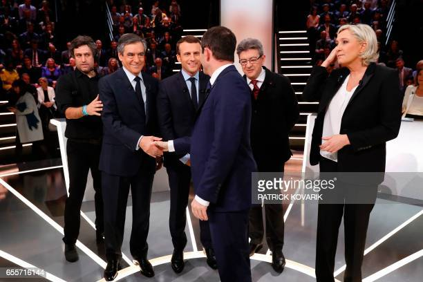 Leftwing French Socialist party Benoit Hamon shakes hands with rightwing Les Republicains party Francois Fillon next to En Marche movement Emmanuel...