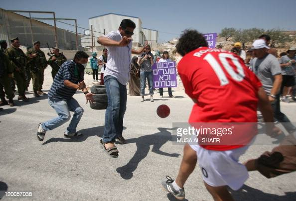 A leftwing Israeli demonstrator holds a sign reading in Hebrew 'Conquer goals not lands' as Palestinian Israeli and foreign peace activists play...