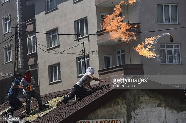 A leftwing militant throws a Molotov cocktail during clashes with Turkish riot police in Istanbul's Gazi district on July 26 2015 Tensions across the...