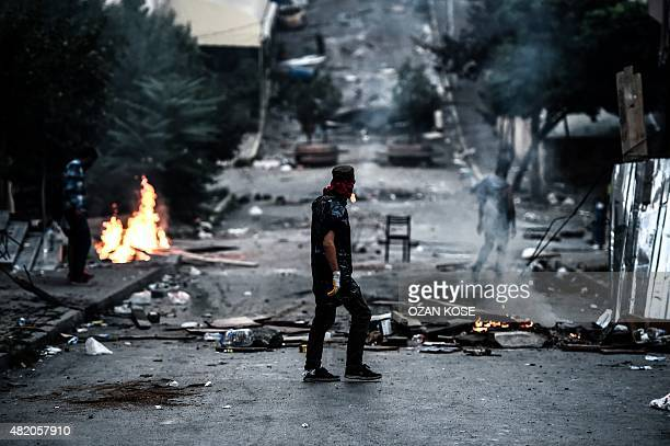 A leftwing protester waits in front of a barricade during clashes with Turkish riot police in the district of Gazi in Istanbul on July 26 2015 A...
