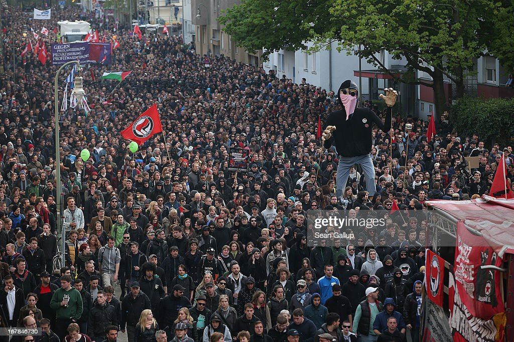 """Left-wing protesters carry a giant puppet as they march in the annual """"Revolutionaerer 1. Mai"""" (Revolutionary May 1st) demonstration on May Day on May 1, 2103 in Berlin, Germany. Several thousand protesters took part in the march that in years past has been plagued by violent clashes between marchers and police."""