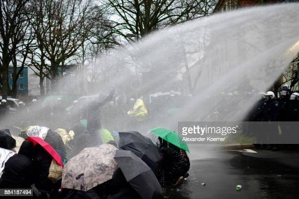 Leftwing protesters get sprayed by a water cannon as they clash with police forces outside the Hannover Congress Centrum prior to today's AfD federal...