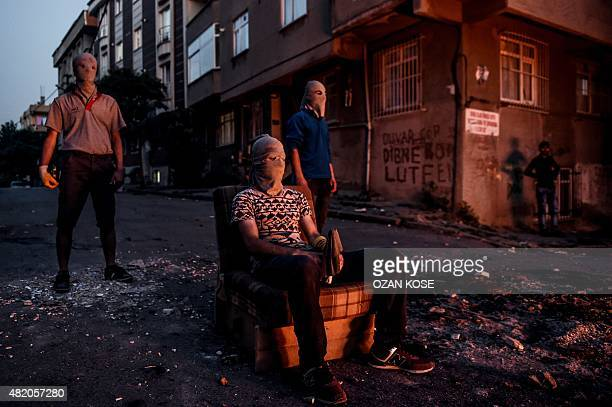Leftwing rotesters with their face hidden wait in front of a barricade during clashes with Turkish riot police in Istanbul's Gazi district on July 26...