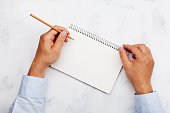Lefty writes in clean notebook on white table top view. International Lefthanders Day. Copy space for text.