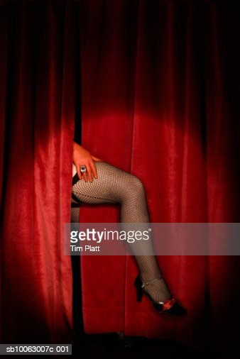 Leg in fishnet stocking appearing from stage curtain : Stock Photo