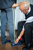 Professional tailor meauring length of male leg