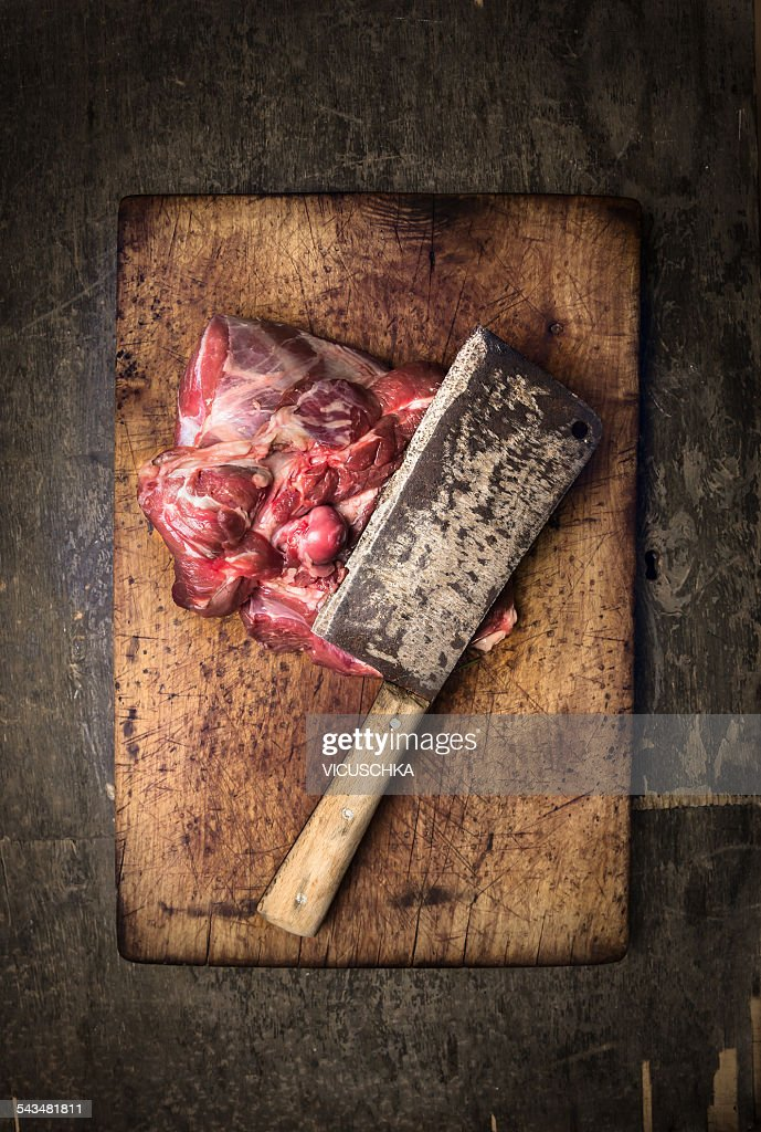 Leg of lamb on chopping board with meat cleaver