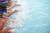 leg shot of kid at swimming pool class learning to swim