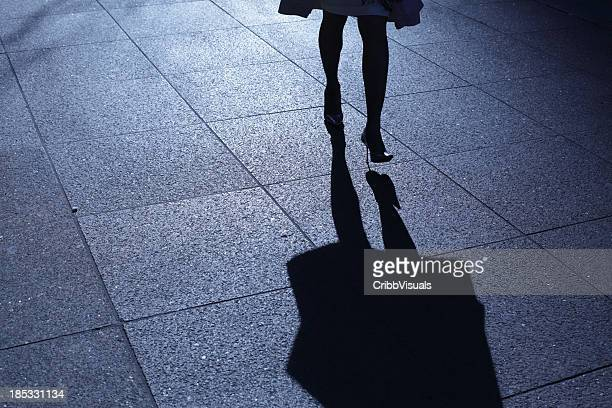 Leg view of a woman in heels walking at night with shadow