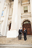 A well dressed man and woman chat and laugh as they walk down steps of a legal or municipal building in discussion. Could be business or legal professionals or lawyer and client or politicians.