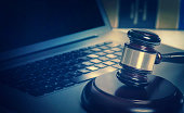 Legal law concept image gavel on computer laptop with book in background