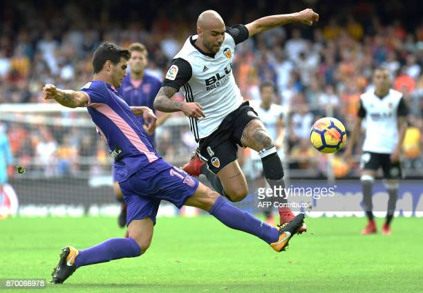Leganes' Argentinian defender Ezequiel Munoz vies with Valencia's Italian forward Simone Zaza during the Spanish league footbal match Valencia CF vs...