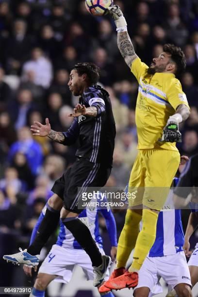 Leganes' goalkeeper Iago Herrerin vies with Real Madrid's defender Sergio Ramos during the Spanish league football match Club Deportivo Leganes SAD...