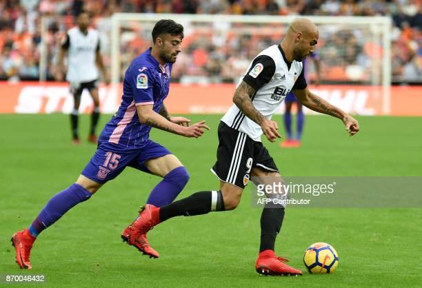 Leganes' Spanish midfielder Diego Rico vies with Valencia's Italian forward Simone Zaza during the Spanish league footbal match Valencia CF vs Club...