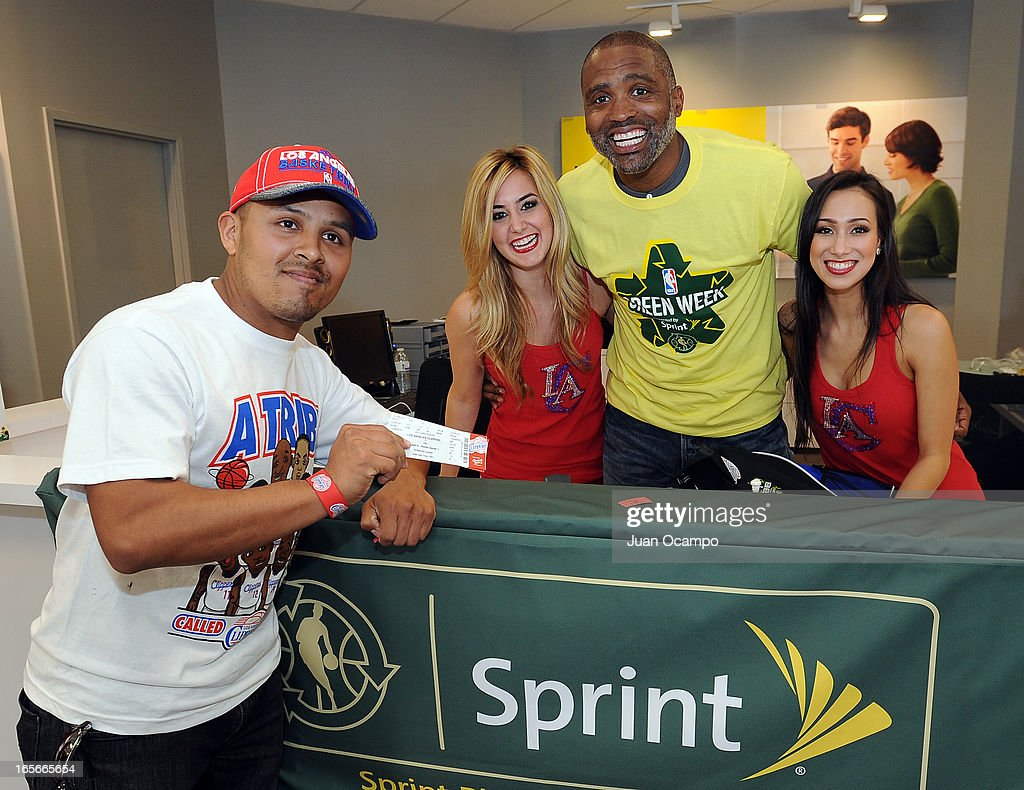 Legend Cuttino Mobley and members of the Clippers Spirit dance team, pose for a photo with a fan who won future Clippers playoff tickets during NBA Green Week presented by Sprint E- Recycling on April 4, 2013 at the Sprint store in Compton, California.