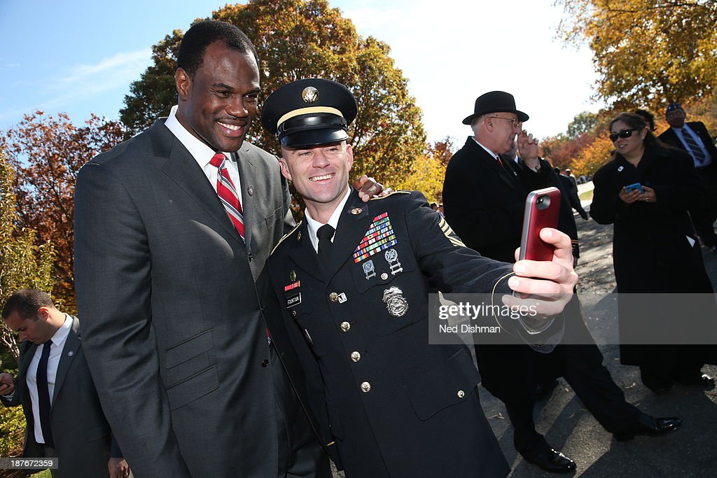 NBA legend David Robinson poses for a photo with an active duty member of the military during Veterans Day ceremonies at Arlington National Cemetery on November 11, 2013 in Washington, DC.