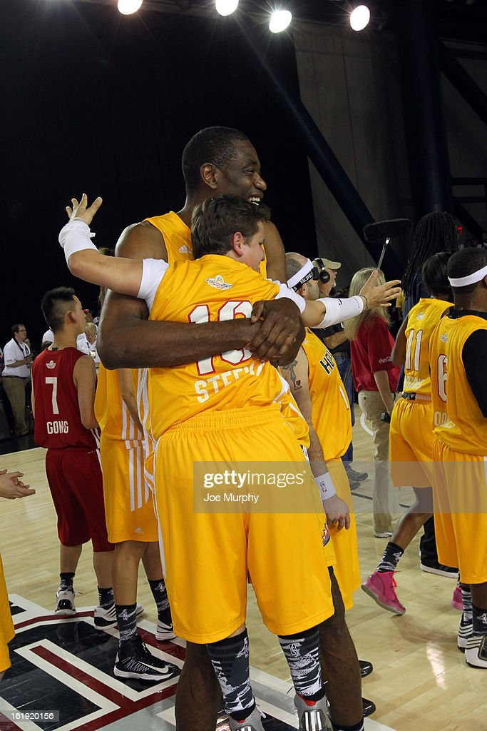 NBA Legend Dikembe Mutombo hugs a teammate during the NBA Cares Special Olympics Unity Sports Basketball Game on Center Court during the 2013 NBA Jam Session on February 17, 2013 at the George R. Brown Convention Center in Houston, Texas.